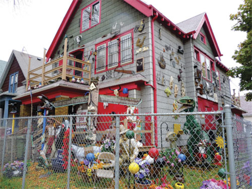 colorful house with lots of junk and knickknacks in yard