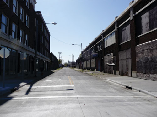deserted street with boarded up buildings on both sides
